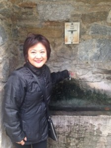 Suzette with hand on faucet, one of four on a stone wall for fresh stream water near Mary's House